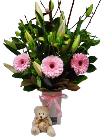 Lovely lilies, gerberas, alstomeria in a ceramic vase with a cute teddy can be made to order for a baby girl or boy.